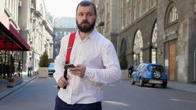 Un homme barbu sur une rue européenne lit des messages dans son smartphone et regarde autour banque de vidéos