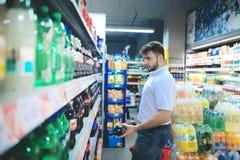 Un homme bel choisit une bouteille de boisson régénératrice de l'étagère de supermarché photo stock