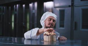 Un homme bel fascinant avec une moustache utilisant un chapeau de cuiseurs, sélectionne avec son doigt à ce gâteau délicieux clips vidéos