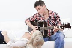 Un homme bel jouant la guitare à une fille mignonne Photos libres de droits