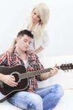 Un homme bel jouant la guitare à une fille mignonne Image libre de droits