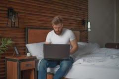 Un homme bel s'assied au bord du lit avec un ordinateur dans des ses mains images stock
