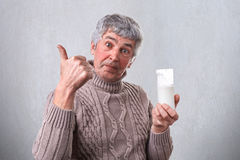 Un homme bel supérieur ayant l'aspect agréable tenant un verre de lait dans sa main prouvant avec son pouce qu'il l'aime Un mA Photo stock