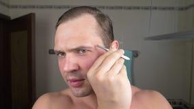 Un homme bel tire ses cheveux hors de ses sourcils avec des brucelles devant un miroir dans la salle de bains Epilation de sourci images stock