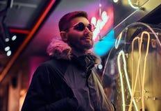 Un homme bel utilisant un manteau et des lunettes de soleil avec des mains dans des poches, se tenant pendant la nuit sur la rue photographie stock libre de droits