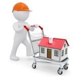 Un homme blanc dans un casque et une maison sur le chariot Photo libre de droits