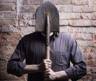 Un homme cache son visage derrière une pelle. images libres de droits