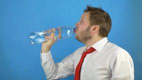 Un homme caucasien avec une barbe dans une chemise blanche et un lien de gueule de bois ouvre une bouteille de l'eau minérale et  clips vidéos