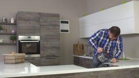 Un homme caucasien satisfait et joyeux avec une barbe entre dans une cuisine moderne et se fait le café noir, mouvement lent banque de vidéos