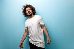 Un homme châtain aux cheveux frisés avec des cheveux de vol utilise un T-shirt blanc asymétrique Caractère facile à vivre et cont photographie stock libre de droits