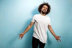Un homme châtain aux cheveux frisés avec des cheveux de vol utilise un T-shirt blanc asymétrique Caractère facile à vivre et cont photos stock