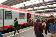Un homme charge une bicyclette dans un train à la station de central de Munich Image libre de droits