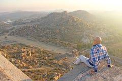 Un homme chauve bel en verres s'assied sur un backgrou de coucher du soleil ou d'aube photos stock