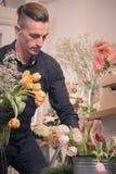 Un homme, choisissant des fleurs, fleuriste Photographie stock libre de droits