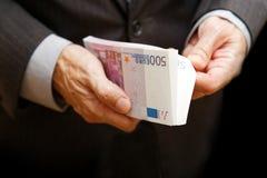 Un homme compte l'argent dans un paquet de billets de banque de 500 euros Images libres de droits