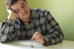 Un homme compte ses pièces de monnaie sur une table photographie stock libre de droits