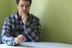 Un homme compte ses pièces de monnaie sur une table photos libres de droits