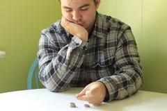 Un homme compte ses pièces de monnaie sur une table images libres de droits