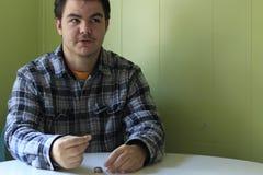 Un homme compte ses pièces de monnaie sur une table photographie stock