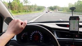 Un homme conduit une voiture à la grande vitesse et tient la roue avec sa main Regarde le navigateur banque de vidéos
