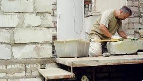 Un homme construit un mur à la maison banque de vidéos