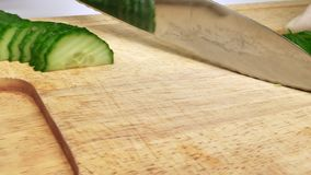 Un homme coupe en tranches des concombres pour la salade Chefcook coupent le concombre de tranches banque de vidéos