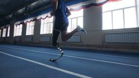 Un homme courant avec la jambe prosthétique, vue de côté banque de vidéos
