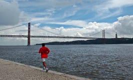 Un homme courant par le Tage à Lisbonne Photographie stock