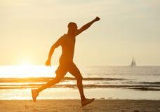 Un homme courant sur la plage avec la main augmentée Image stock