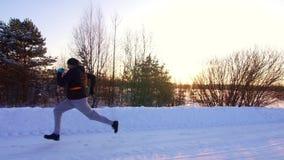 Un homme court le long d'une route neigeuse, d'un paysage d'hiver et du coucher de soleil banque de vidéos