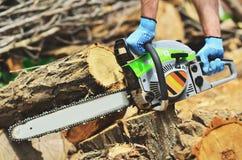 Un homme court une tronçonneuse, enlève un morceau de bois image libre de droits