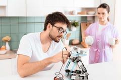 Un homme crée un robot dans la cuisine Son amie est se tenante prêt et versante le thé Images stock