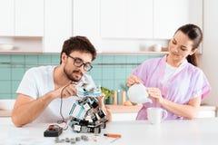 Un homme crée un robot dans la cuisine Son amie est se tenante prêt et versante le thé Photo stock