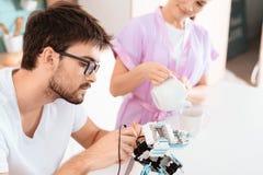 Un homme crée un robot dans la cuisine Son amie est se tenante prêt et versante le thé Photographie stock libre de droits