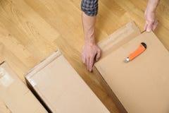 Un homme déballe les boîtes en carton image stock