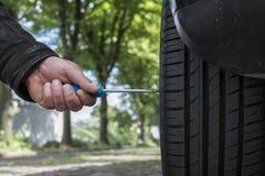Un homme démolit un pneu de voiture photo stock