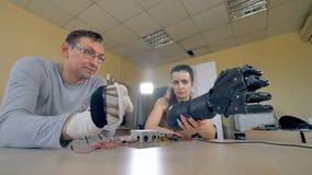 Un homme déplaçant sa main, bras bionique répétant le sien se déplace