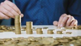 Un homme déplace une colonne des pièces de monnaie banque de vidéos