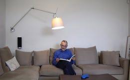 Un homme détendant et lisant sur un sofa Photos libres de droits