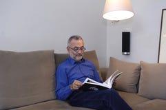 Un homme détendant et lisant sur un sofa Images libres de droits