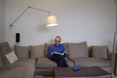 Un homme détendant et lisant sur un sofa Photos stock