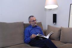 Un homme détendant et lisant sur un sofa Photo stock