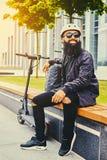 Un homme détendant sur un banc après la monte en le scooter électrique image libre de droits