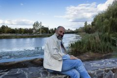 Un homme d'âge mûr s'assied sur un piédestal en pierre moitié-tourné Photo stock