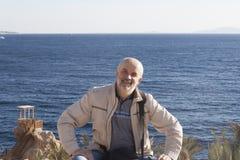 Un homme d'âge mûr sur la plage sur le fond du Se rouge Photos libres de droits