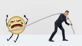Un homme d'affaires écartant grande une pièce de monnaie d'or peu disposée et pleurante avec une corde photographie stock libre de droits