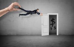 Un homme d'affaires étant traîné à partir d'une porte menant à une salle avec les dollars peints par une main géante photographie stock