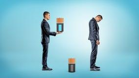 Un homme d'affaires apporte une grande batterie entièrement chargée pour remplacer épuisé de l'intérieur d'un homme d'affaires tr Photos libres de droits