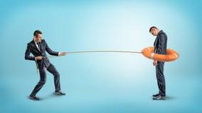 Un homme d'affaires attrape un autre homme avec une balise de vie orange utilisée comme lasso Photos stock