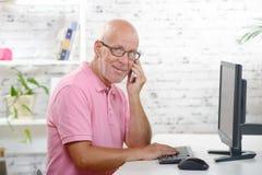 Un homme d'affaires au téléphone dans son bureau Photographie stock